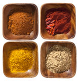 Four ground up spices in wooden bowels Stock Images