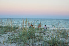 Four guys on the beach with binocular in the evening Stock Images