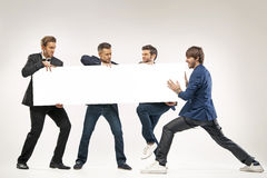 Four guys pushing the billboard. Four friends pushing the billboard Royalty Free Stock Images