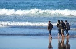 Four guys walking on the beach. Group of boys, four guys walking on the beach royalty free stock photos