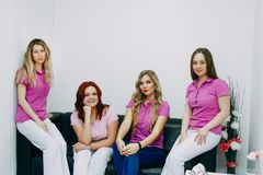 Four hairdressers posing in the Barber shop royalty free stock images