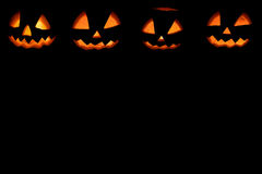 Four halloween pumpkins background. On black Royalty Free Stock Image