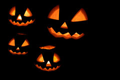 Four halloween pumpkins wallpaper. On black Royalty Free Stock Image
