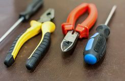 Four hand tools home repair furniture electricians base two screwdrivers pliers and nippers close-up on a dark background stock photos