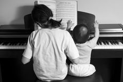 Four hands. Children playing piano (BW), back view Stock Image
