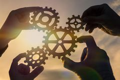 Four hands of businessmen collect gear from the gears of the details of puzzles. royalty free stock photo