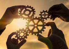 Four hands of businessmen collect gear from the gears of the details of puzzles. Against the background of sunlight. The concept of a business idea. Teamwork stock photos