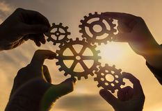 Four hands collect the gear from the gears of the details of the puzzles. Against the background of sunlight. Concept business idea. Teamwork royalty free stock photos