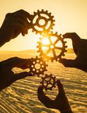 Four hands collect the gear from the gears of the details of the puzzles. Against the background of sunlight. Concept business idea. Teamwork royalty free stock images