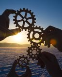 Four hands collect the gear from the gears of the details of the puzzles. Against the background of sunlight. Concept business idea. Teamwork. Close-up Royalty Free Stock Images