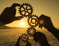 Four hands collect the gear from the gears of the details of the puzzles. Against the background of sunlight. Concept business idea. Teamwork stock images