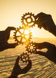 Four hands collect the gear from the gears of the details of the puzzles. Against the background of sunlight. Concept business idea. Teamwork stock image