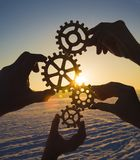 Four hands collect the gear from the gears of the details of the puzzles. Against the background of sunlight. Concept business idea. Teamwork royalty free stock photo