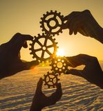Four hands collect the gear from the gears of the details of the puzzles. Stock Images