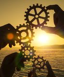 Four hands collect the gear from the gears of the details of the puzzles. Against the background of sunlight. Concept business idea. Teamwork stock photography