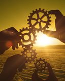 Four hands collect the gear from the gears of the details of the puzzles. Against the background of sunlight. Concept business idea. Teamwork. Close-up royalty free stock photos