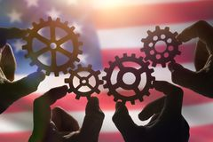 Four hands collect a puzzle of gears, against the background of the sky at sunset. Business concept idea. Strategy cooperation, teamwork, creativity royalty free stock photo