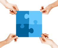 Four hands connecting puzzle pieces. Business, teamwork and collaboration concept - four hands connecting blue puzzle pieces royalty free stock photography