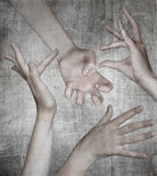 Four hands on gray background Royalty Free Stock Image