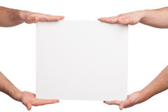 Four hands holding a blank white board Stock Photo
