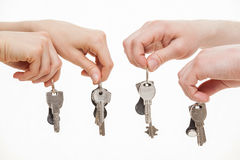 Four hands holding bunches of keys. White background Stock Photo