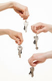 Four hands holding bunches of keys. White background Royalty Free Stock Photography