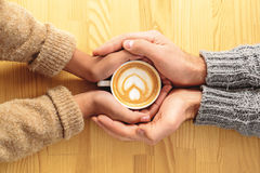 Four hands holding a coffee cup Royalty Free Stock Photography