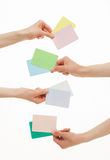 Four hands holding colorful paper cards Royalty Free Stock Photo