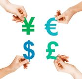 Four hands holding currency symbols. Investment, stock market and exchange concept - four hands holding currency symbols Stock Photos