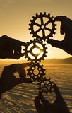 Four hands are holding the gears against the sunset. Teamwork. harmonious work Royalty Free Stock Photography