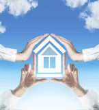 Four hands holding house Stock Photo