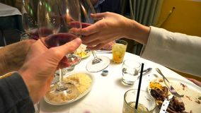Four hands holding red wine and cheers. Four hands holding red wine and doing cheers to celebrate in a restaurant stock footage