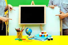 Empty chalkboard hand School notebook board male female paint globe pencils table four show yellow blue royalty free stock photos