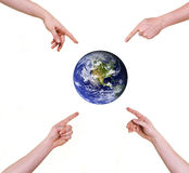 Four hands pointing fingers at planet earth Royalty Free Stock Image