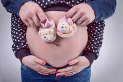 Four hands on a pregnant belly. Four hands on pregnant belly with pink ribbon Stock Photos