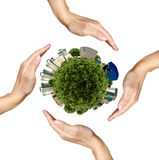 Four hands saving the miniature earth on white Royalty Free Stock Photos