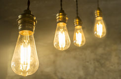 Four hanging light bulbs over oxide dark color concrete backgrou Stock Photo