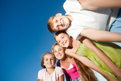 Four happy beautiful children looking at camera from top in the sunny summer day and blue sky. looking at camera with funny face a Royalty Free Stock Photo