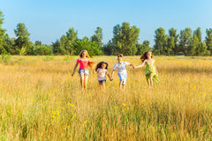 Four happy beautiful children running playing moving together in the beautiful summer day. Jumping and looking at camera with happiness and toothy smile Royalty Free Stock Photos