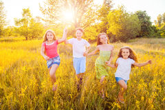 Four happy beautiful children running playing moving together in the beautiful summer day. Royalty Free Stock Photography