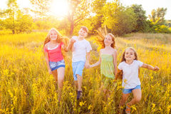 Four happy beautiful children running playing moving together in the beautiful summer day. Jumping and looking at camera with happiness and toothy smile Royalty Free Stock Photography
