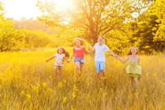 Four happy beautiful children running playing moving together in the beautiful summer day. Jumping and looking at camera with happiness and toothy smile Stock Photos
