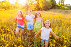 Four happy beautiful children running playing moving together in the beautiful summer day. Stock Image