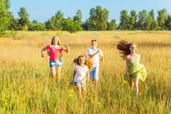 Four happy beautiful children running playing moving together in the beautiful summer day. Jumping and looking at camera with happiness and toothy smile Royalty Free Stock Photo