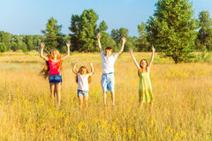 Four happy beautiful children running playing moving together in the beautiful summer day. Jumping and looking at camera with happiness and toothy smile Stock Images