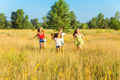 Four happy beautiful children running playing moving together in the beautiful summer day. Jumping and looking at camera with happiness and toothy smile Stock Image
