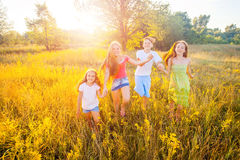 Four happy beautiful children running playing moving together in the beautiful summer day. Jumping and looking at camera with happiness and toothy smile Stock Photography