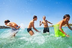 Four happy boys playing at tropical shallow water stock images