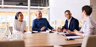Four happy business people smiling during their weekly meeting together Royalty Free Stock Photo