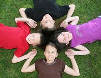 Four Happy Children. 4 Happy Children Lying in the Grass Stock Photo